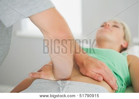 Physiotherapist checking patients pelvis alignment in bright office