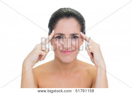 Wincing bare brunette touching her temples on white background