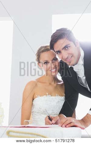 Handsome young bridegroom signing wedding contract smiling at camera