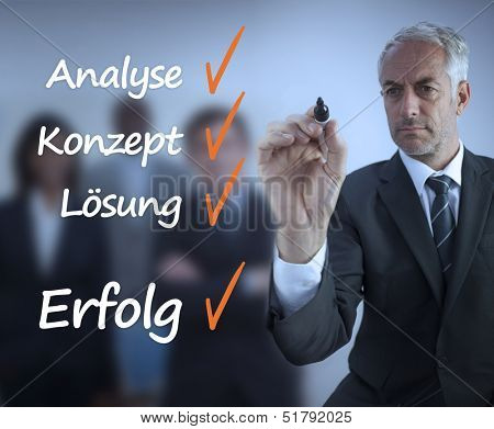 Businessman writing a success checklist in german in front of business team