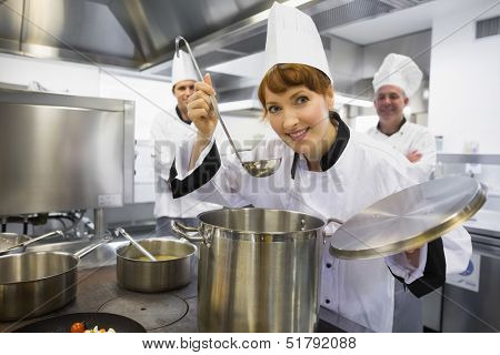 Young female chef tasting a soup and smiling at camera in kitchen
