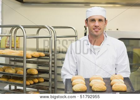 Happy young baker holding some rolls on a baking tray smiling at the camera