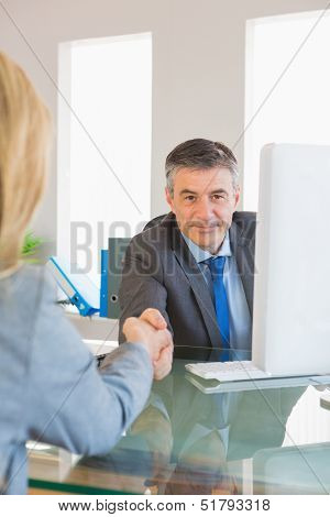 Content mature businessman shaking the hand of a blonde interviewee in office