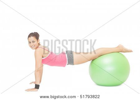 Smiling sporty brunette doing exercise with exercise ball on white background