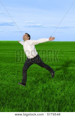 Running Businessman In The Meadow Over Clouds Background