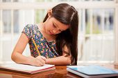 stock photo of homework  - Beautiful little girl looking focused and concentrated on doing her homework - JPG