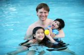 stock photo of mixed race  - Father and his two children enjoying the pool - JPG