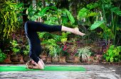 stock photo of ashtanga vinyasa yoga  - Yoga shirshasana headstand pose by young woman in black costume in the garden with banana trees and tropical plants in the pots - JPG
