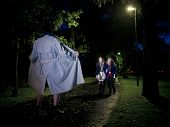 stock photo of obscene  - Two women laughing at a Flasher at night in the park - JPG