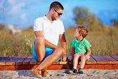 foto of father time  - smiling father and son talking summer outdoor - JPG