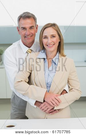 Happy businessman embracing woman from behind in the kitchen at home