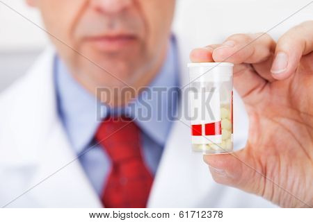 Doctor Holding A Pill Container At Drug Store