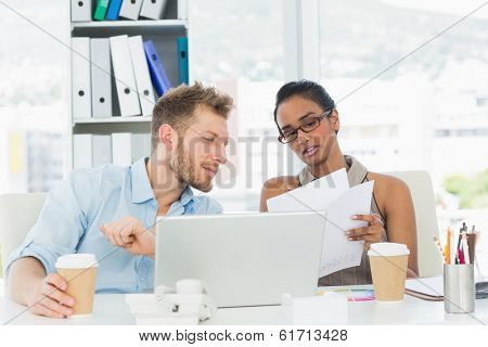 Partners working together on laptop at desk in creative office