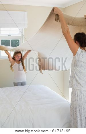 Mother and daughter making bed together in house