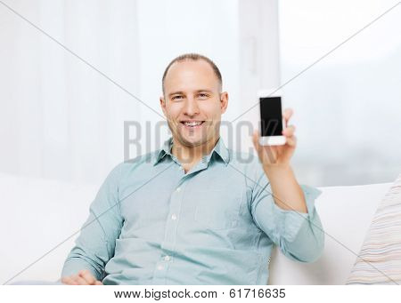 business, communication, home and modern technology concept - smiling man with smartphone at home