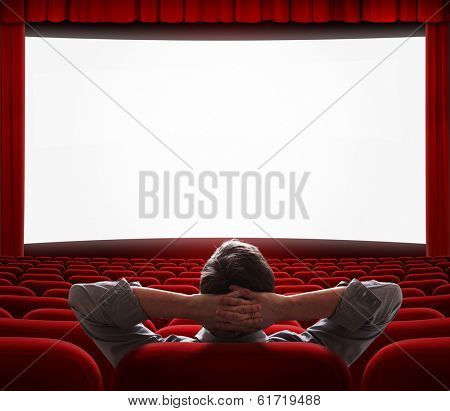 one relaxed man sitting alone with comfort like at home in front of big screen in empty cinema hall