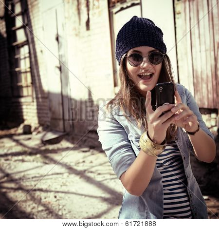 Pretty young woman using mobile phone and getting photos, outdoor. Toned.