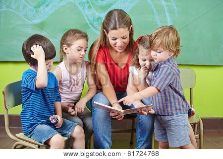 Children and nursery teacher reading book together in kindergarten