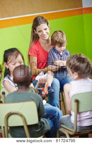 Children in kindergarten sitting in circle and reading book with nursery teacher