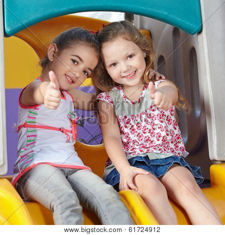 Two happy girls in kindergarten holding her thumbs up