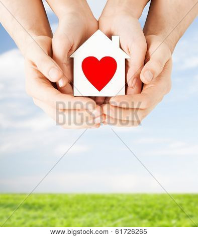 charity, real estate and family home concept - closeup picture of male and female hands holding white paper house with red heart