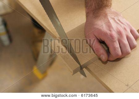 Carpenter Sawing  Wood In Workshop