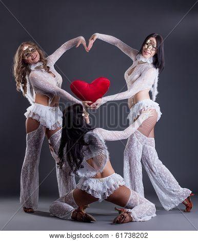 Trio of beautiful go-go dancers posing as cupids