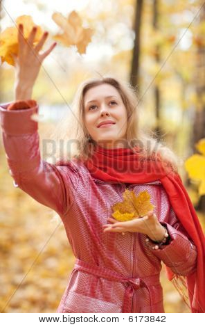 Young Woman Throwing Leaves