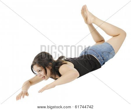 An attractive young teen moving down through the air hands and head first.  On a white background.