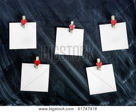 Paper Cards Attached With Clothes Pins With Small Hearts To The Chalkboard