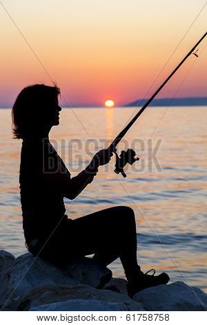 Woman silhouette fishing on rock