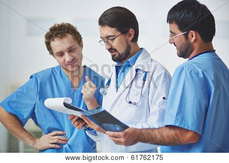 Portrait of three clinicians in uniform discussing document