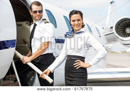 Portrait of beautiful airhostess with pilot boarding private jet
