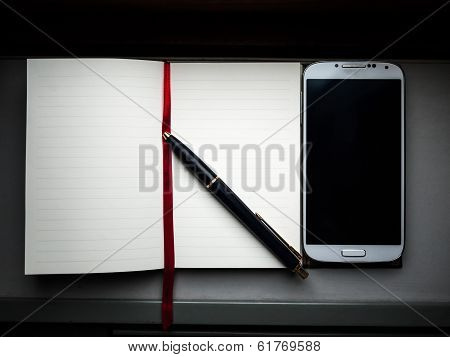 Notebook With A Pen On The Side And A Smartphone