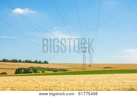 High-voltage Towers And Cables In Agricultural Fields On A Blue Sky Background