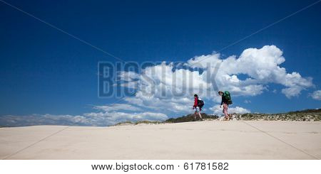 Two female hikers on sunny beach