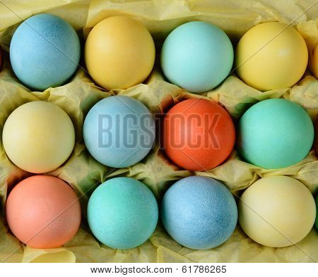 Closeup of an Easter Egg Carton on a rustic farmhouse kitchen table. The carton is lined with yellow tissue paper. Horizontal format.