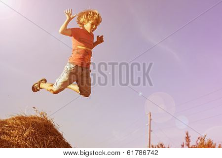 Boy jumping with haystacks.