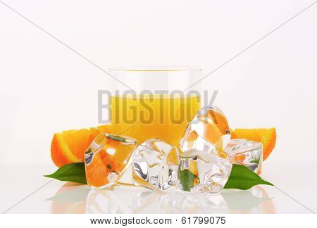 orange juice in the glass, surrounded with ice cubes and fresh oranges with leaves