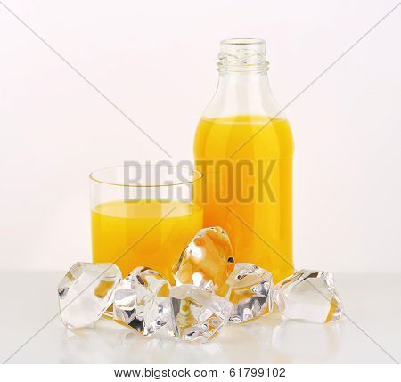 glass and bottle filled with orange juice, decorated with ice cubes