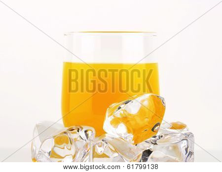 glass of orange juice with frozen ice cubes