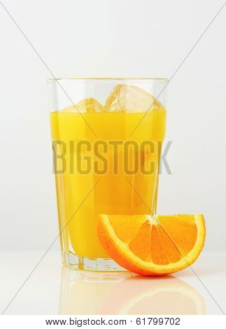 glass of cold juice and fresh piece of orange