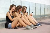 foto of adolescent  - Group of teenager girls smiling happy texting on the smart phone sitting on the floor outdoors - JPG