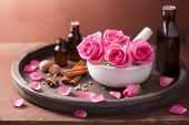 stock photo of perfume  - spa and aromatherapy set with rose flowers mortar and spices - JPG