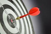 stock photo of bullseye  - Meet target concept using dart pinned at the bullseye of dartboard - JPG