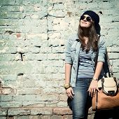 image of singer  - beautiful cool girl in hat and sunglasses against grunge wall - JPG