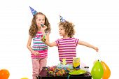 stock photo of three sisters  - Little girls sisters at birthday party with cake and balloons against white background - JPG