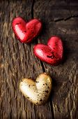 image of heartfelt  - Decorative red and gold hearts on a wooden background