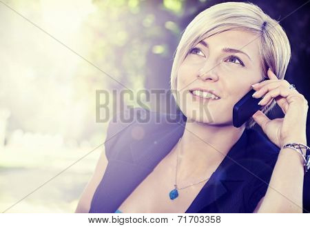 Smiling blond woman on the call outdoors, using cell phone looking up.
