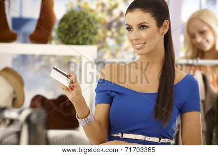 Beautiful woman paying by credit card at clothes store, smiling.